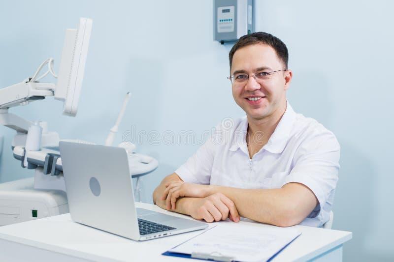 Жизнерадостный доктор сидя на офисе ` s доктора с компьтер-книжкой стоковое изображение rf