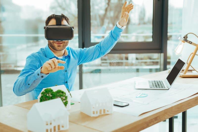 Жизнерадостный инженер усмехаясь и работая с виртуальной реальностью стоковое фото rf