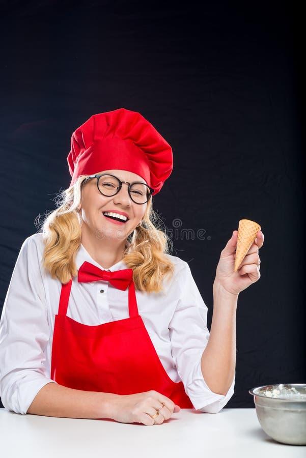 Жизнерадостный кашевар с мороженым в красном костюме стоковое изображение