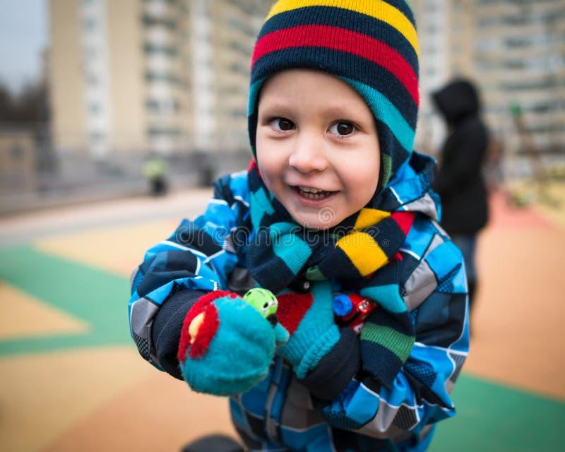 Жизнерадостный мальчик бежит вокруг на спортивной площадке и имеет потеху стоковые изображения rf