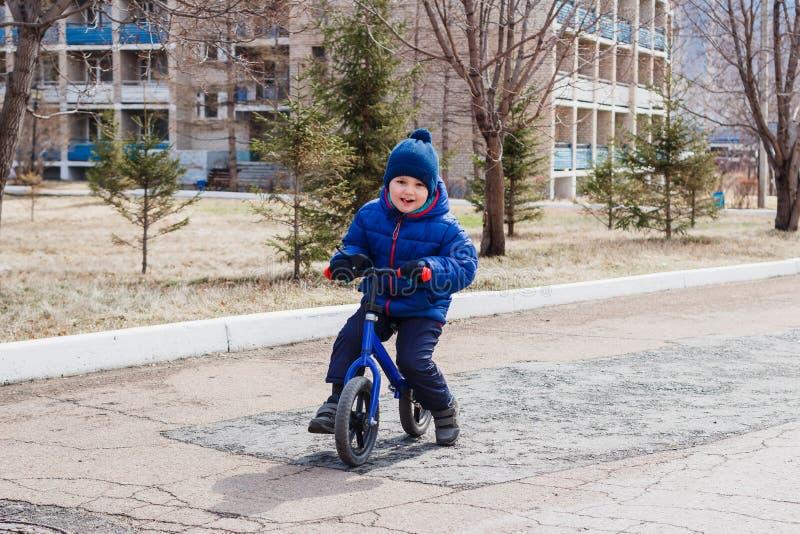 Жизнерадостный мальчик в теплых одеждах ехать велосипед детей идущий в предыдущей весне стоковые изображения rf