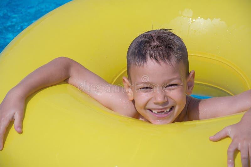 Жизнерадостный мальчик наслаждается плыть на раздувное кольцо в бассейне стоковая фотография rf