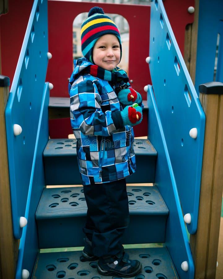 Жизнерадостный мальчик стоит на лестнице на спортивной площадке стоковые изображения rf