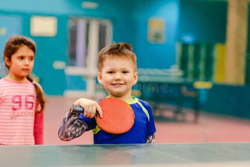 Жизнерадостный мальчик стоя в зале тенниса, зала тенниса, te стоковые фотографии rf