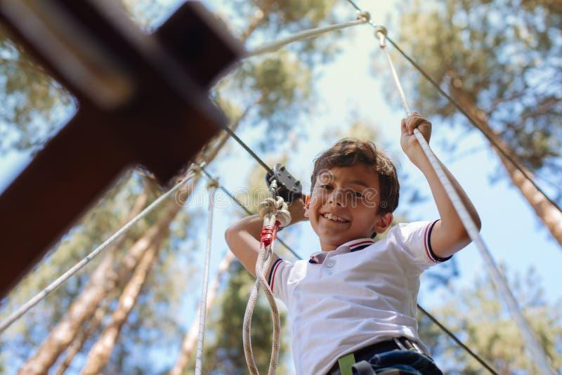 Жизнерадостный мальчик preteen усмехаясь от пробы парка веревочки стоковое изображение rf