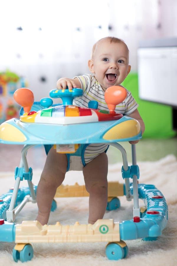 Жизнерадостный младенец в ходоке младенца в живущей комнате стоковые изображения