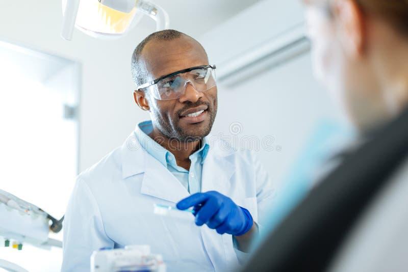 Жизнерадостный молодой дантист говоря о зубоврачебной металлической пластинке стоковая фотография