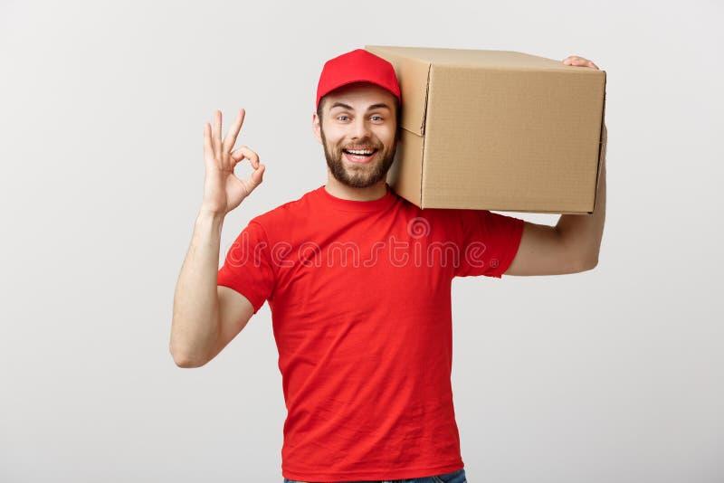 Жизнерадостный молодой работник доставляющий покупки на дом в красной крышке стоя при коробка столба пакета изолированная над бел стоковое фото rf