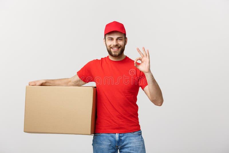 Жизнерадостный молодой работник доставляющий покупки на дом в красной крышке стоя с коробкой столба пакета над белым жестом о'кей стоковое изображение