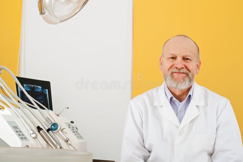 Жизнерадостный мужской дантист в офисе стоковое фото rf