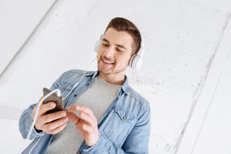 Жизнерадостный мужск человек используя его устройство с удовольствием стоковые изображения