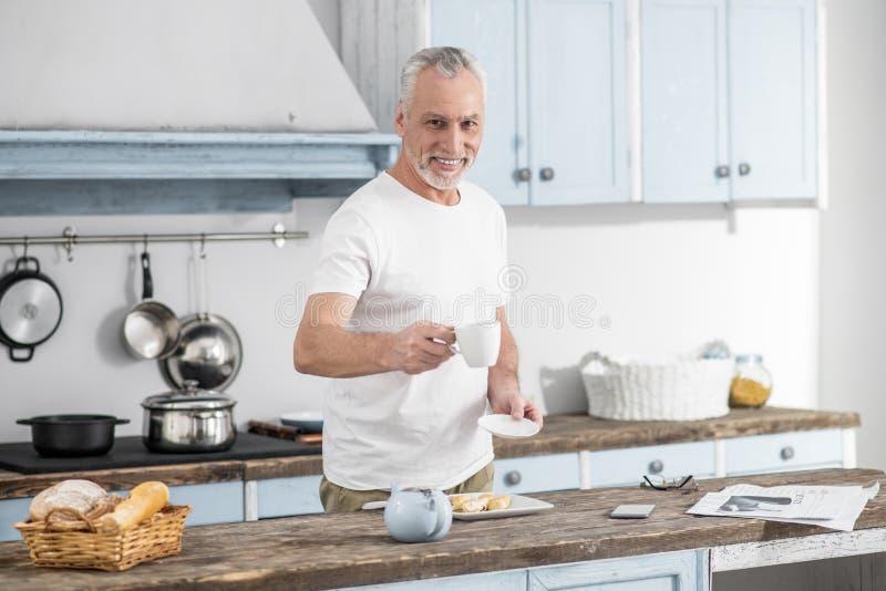 Жизнерадостный мужск человек предлагая кофе к вам стоковое изображение
