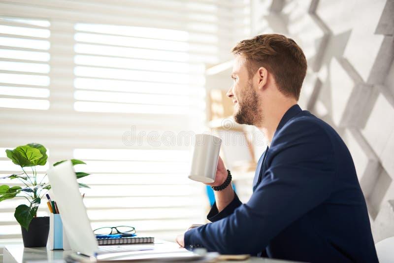 Жизнерадостный мужчина восхищая горячее питье на настольном компьютере стоковое изображение rf