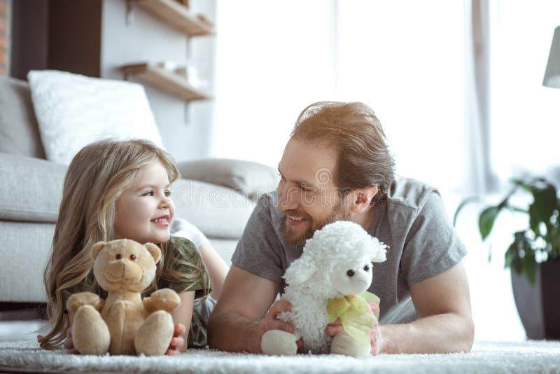 Жизнерадостный отец и дочь имея потеху с игрушками стоковые фотографии rf