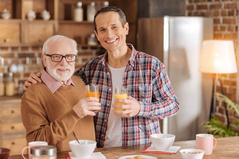 Жизнерадостный отец и сын представляя с стеклами сока стоковое изображение