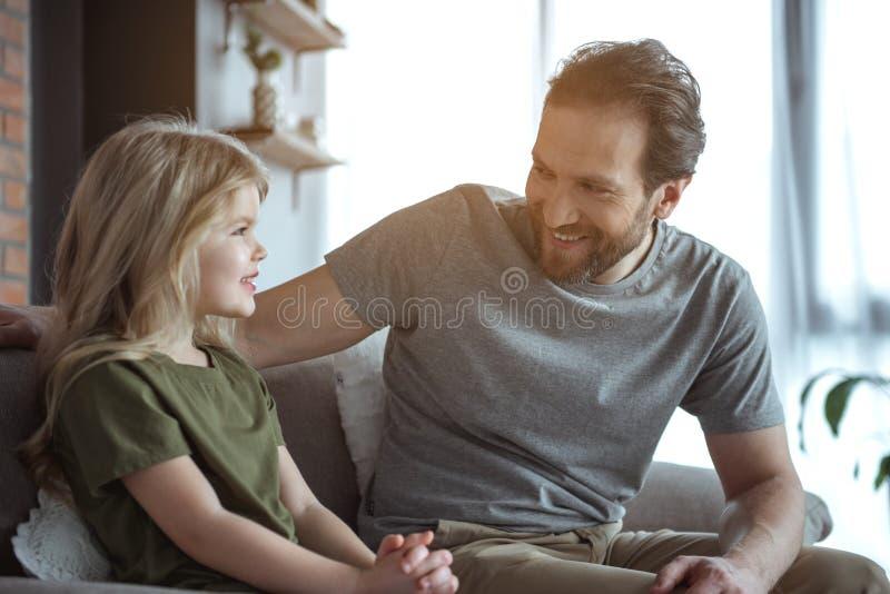 Жизнерадостный папа разговаривая с его ребенком в квартире стоковое фото