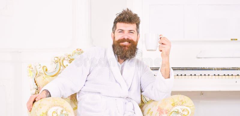 Жизнерадостный парень в белом купальном халате наслаждаясь кофе утра Бородатый человек сидя в красивом античном кресле напористо стоковые фотографии rf
