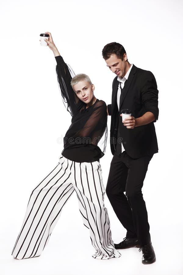Жизнерадостный парень в черном костюме и девушка на белой предпосылке шаловливой, танцующ с кофейными чашками стоковые фото