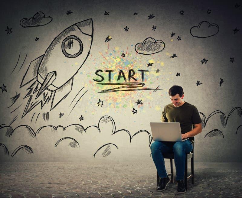 Жизнерадостный положительный парень играя видеоигры на его ноутбуке как начала корабля ракеты, принимая в космос стоковые фотографии rf