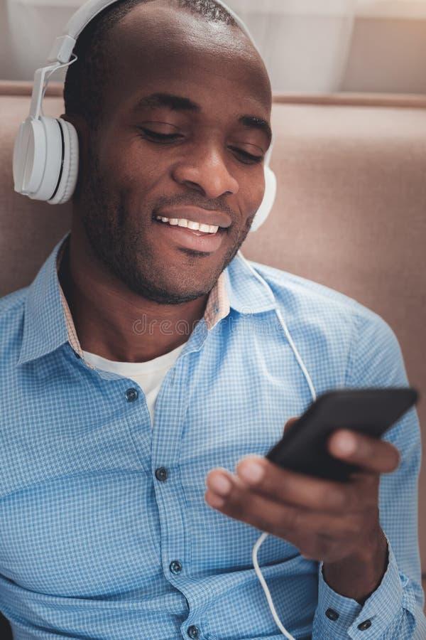 Жизнерадостный положительный человек смотря экран смартфона стоковое фото