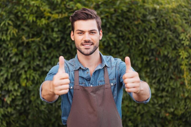 Жизнерадостный садовник в рисберме показывая большие пальцы руки вверх и смотря камеру стоковое фото rf