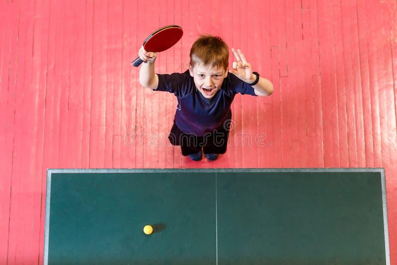 Жизнерадостный семилетний ребенок наслаждается выиграть настольный теннис, взгляд сверху Зеленая таблица настольного тенниса стоковая фотография