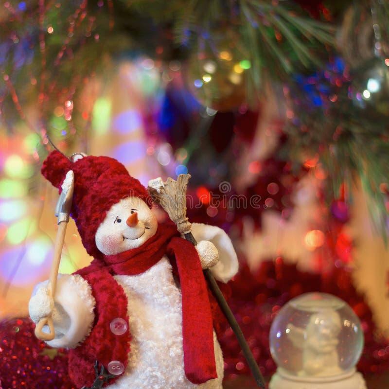 Жизнерадостный снеговик с веником и лопаткоулавливателем против предпосылки bokeh стоковые изображения