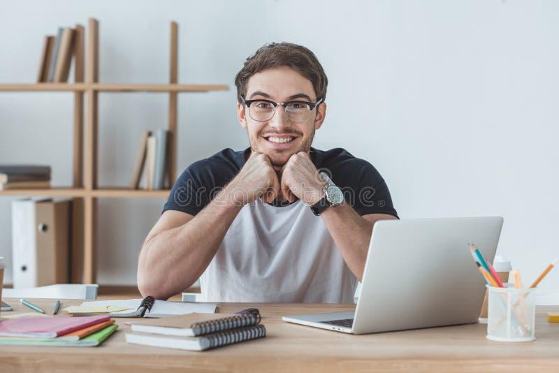 жизнерадостный студент сидя на таблице с тетрадями стоковые фотографии rf