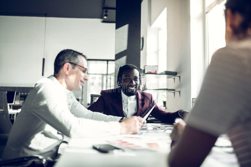 Жизнерадостный темнокожий коллега усмехаясь смотрящ его секретаршу стоковое изображение