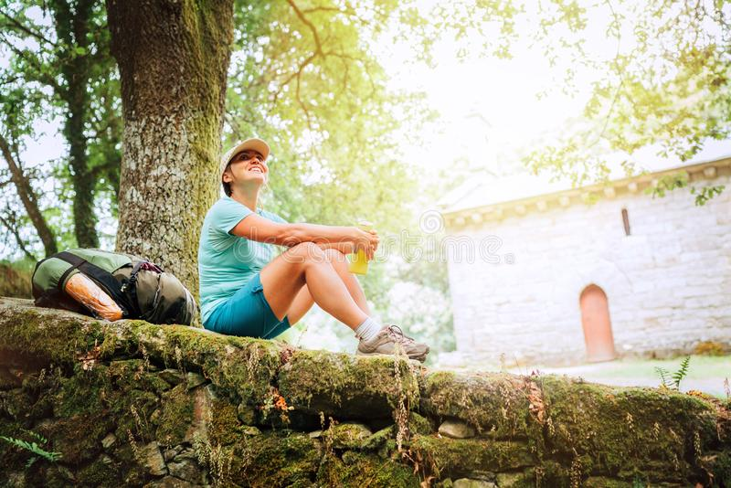 Жизнерадостный усмехаясь молодой женский backpacker сидя на старом каменном fance замка и наслаждаясь временем остатков на пути C стоковые изображения rf