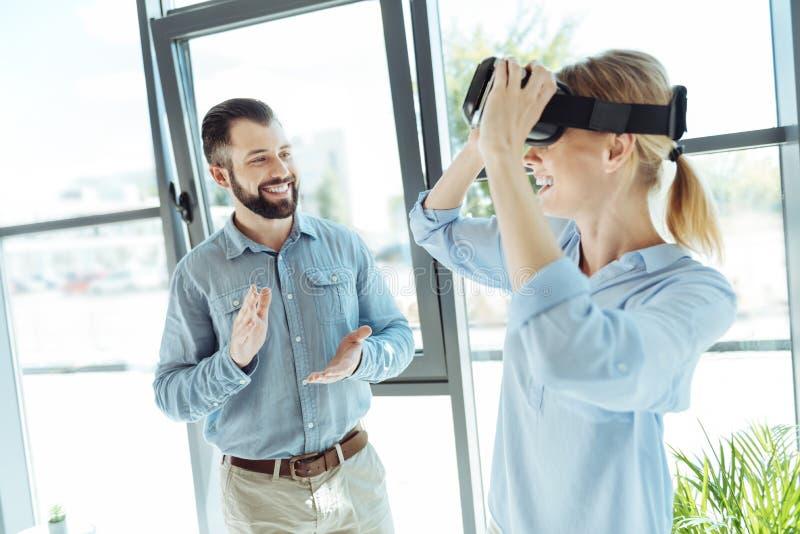Жизнерадостный человек давая рукоплескание к коллеге извлекая шлемофон VR стоковые изображения rf