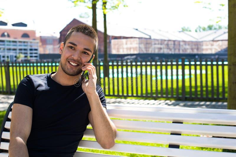 Жизнерадостный человек имея приятный телефонный разговор клетки стоковое фото