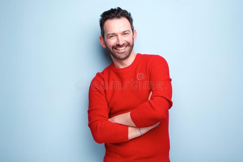 Жизнерадостный человек при борода представляя против голубой предпосылки стоковая фотография rf