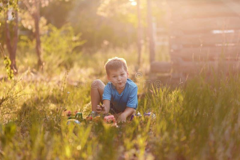 Жизнерадостный эмоциональный пятилетний мальчик в голубой футболке и шортах сидя на траве летом и играя с игрушками стоковые фото