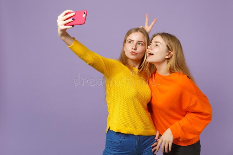 2 жизнерадостных молодых белокурых девушки сестер близнецов в красочных одеждах делая selfie снятое на мобильном телефоне изолиро стоковая фотография rf