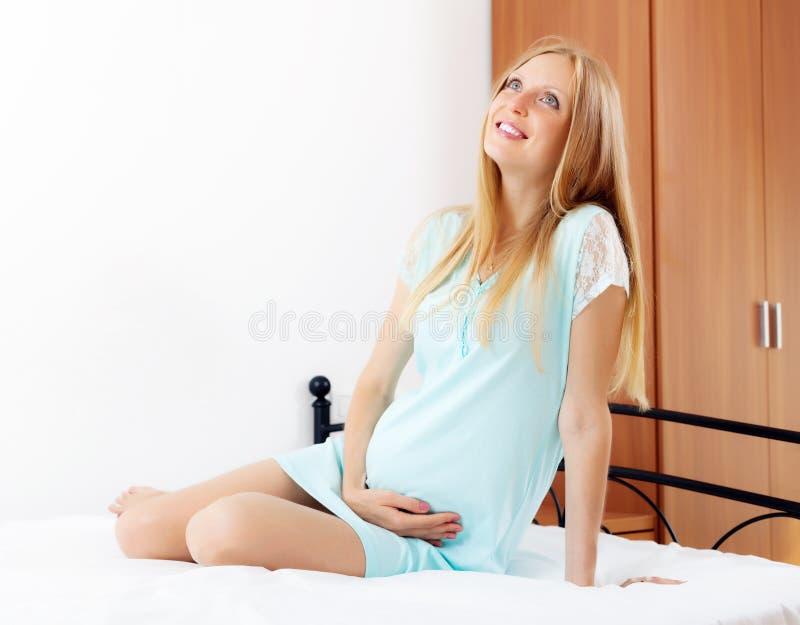 Жизнерадостная беременная женщина сидя в кровати стоковые фотографии rf