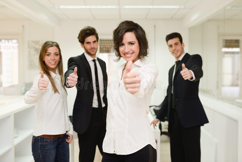 Жизнерадостная бизнес-группа давая большие пальцы руки вверх стоковые изображения