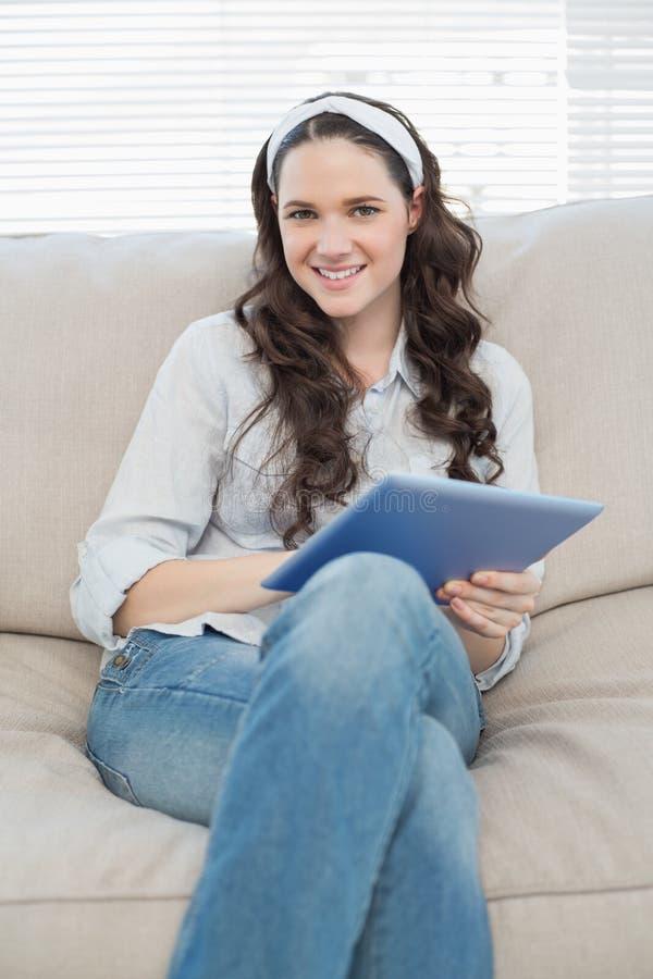 Жизнерадостная вскользь женщина на cosy кресле используя ПК таблетки стоковое фото rf