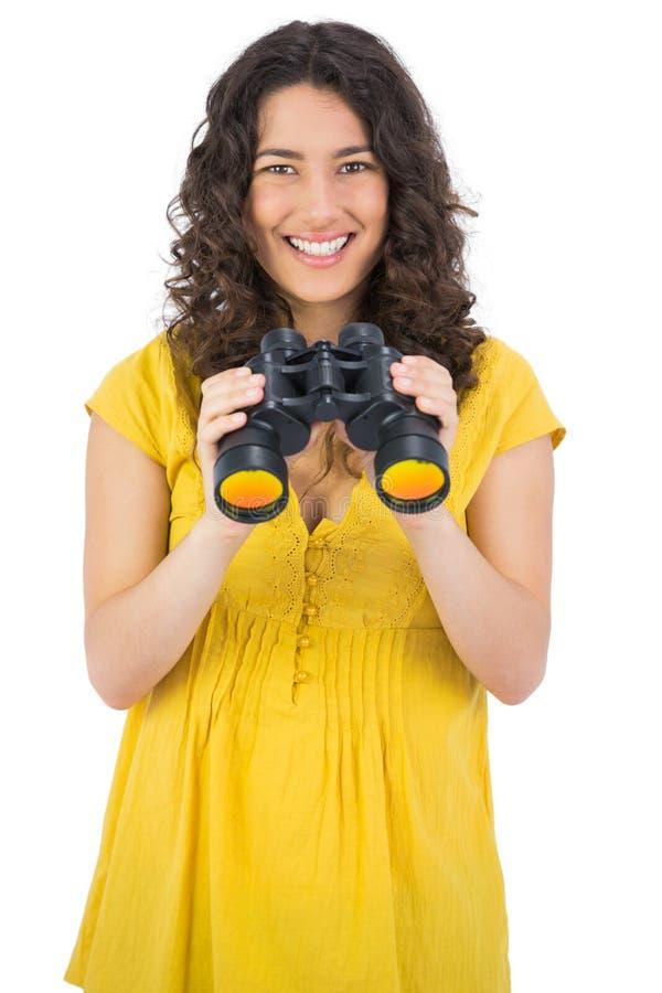 Жизнерадостная вскользь молодая женщина используя бинокли стоковая фотография rf