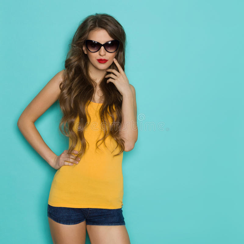 Жизнерадостная девушка в солнечных очках на предпосылке Teal стоковое изображение