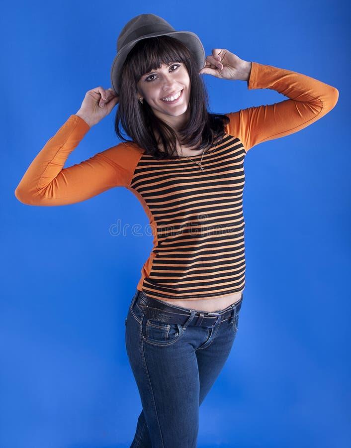 Жизнерадостная девушка в шляпе на голубой предпосылке стоковая фотография