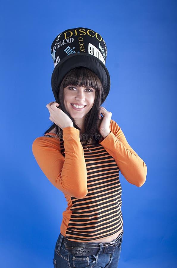 Жизнерадостная девушка в шляпе на голубой предпосылке стоковое фото rf
