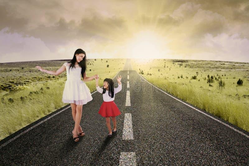Жизнерадостная девушка и ее мать на дороге стоковые фотографии rf