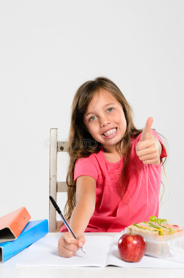 Жизнерадостная девушка начальной школы делает ее домашнюю работу стоковое фото rf