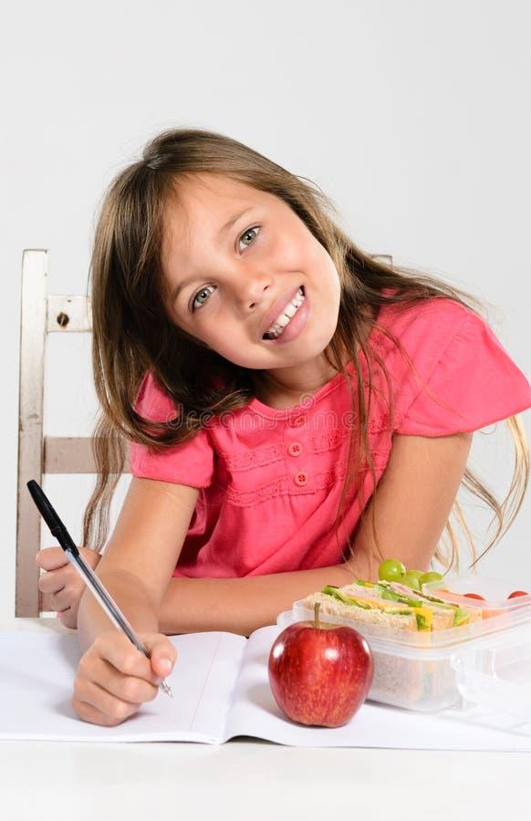 Жизнерадостная девушка начальной школы делает ее домашнюю работу стоковые изображения
