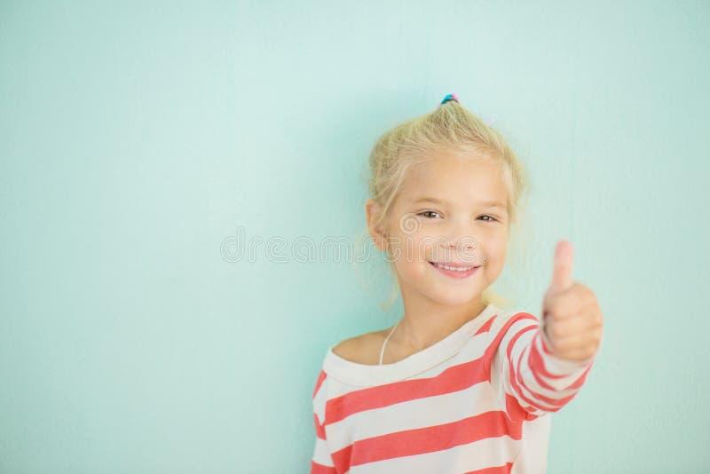 Жизнерадостная девушка поднимает большой палец руки вверх стоковое фото rf