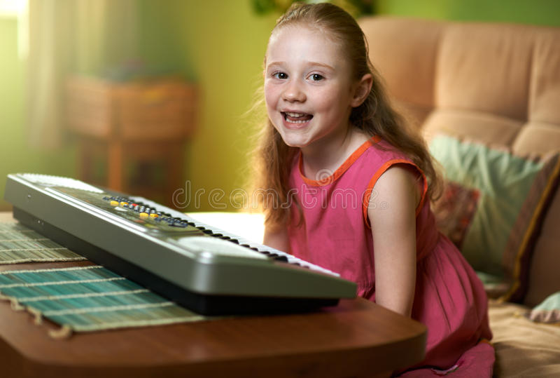 Жизнерадостная девушка сидит около электронного рояля стоковое изображение rf
