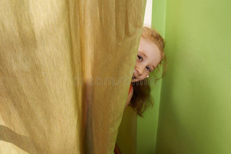 Жизнерадостная девушка смотрит вне от задних занавесов стоковые фото