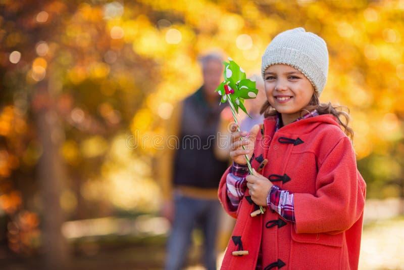 Жизнерадостная девушка с игрушкой pinwheel на парке стоковое фото