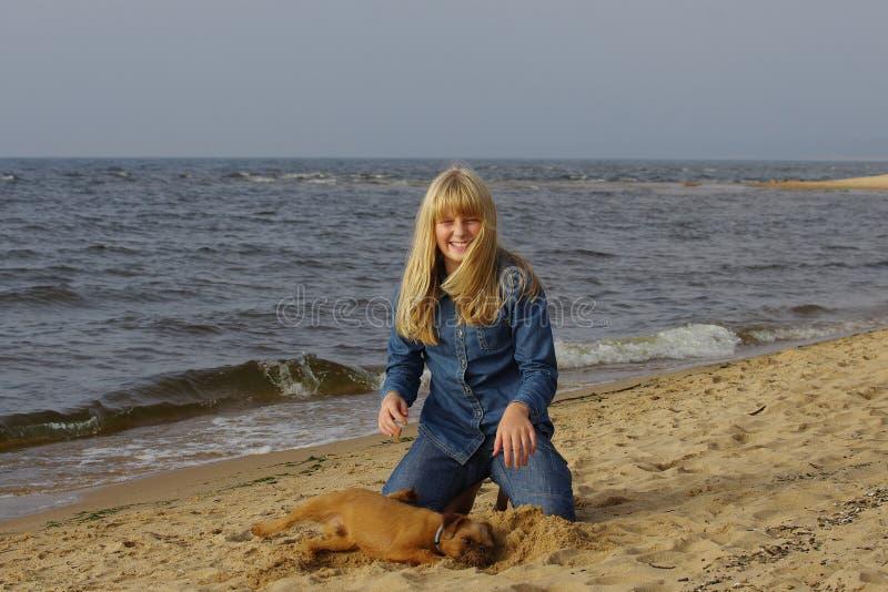 Жизнерадостная девушка с собакой морем стоковые фотографии rf